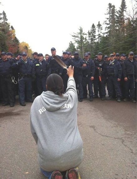 An Ilnu grandmother, after being pepper sprayed, kneels down in front of police as they move in to arrest people at the blockade against shale gas in Rexton. Photo by Ossie Michelin.