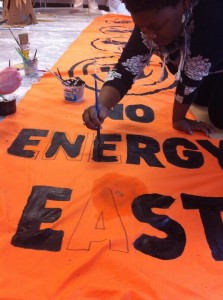 PowerShift participants paint a banner against the Energy East pipeline. Photo by Robin Tress.