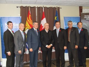 """The government of New Brunswick and Oxford Frozen Foods announced a deal to develop wild blueberry fields and a processing plant in northern New Brunswick on Oct. 31. Invest NB attracts multinational corporations to do business as usual in New Brunswick, """"creating jobs"""" in exchange for corporate welfare incentives.  Such doling out of public monies to multinationals is according to script, for InvestNB was set up to do precisely that, rather than offer support to New Brunswick based businesses, including co-operatives. Local blueberry growers and locals are concerned how the project will impact local growers and the environment as forest land is cleared for the crops. From left to right: Nepisiguit MLA Ryan Riordon; Tracadie-Sheila MLA Claude Landry; Premier David Alward; John Bragg, founder, chair, co-chief executive officer and president of Oxford Frozen Foods; Natural Resources Minister Paul Robichaud; Tracadie-Sheila Mayor Aldeoda Losier; and Miramichi Bay-Neguac MLA Serge Robichaud. Photo from the Government of New Brunswick."""